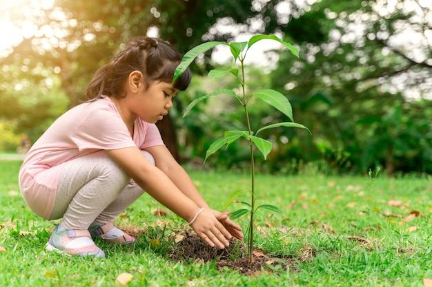 Niña asiática plantando un árbol en suelo negro para reducir la situación del calentamiento global