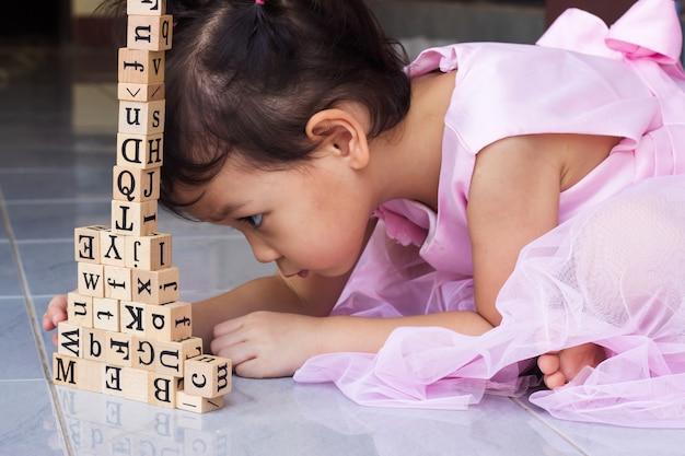 Niña asiática que construye el bloque de madera.