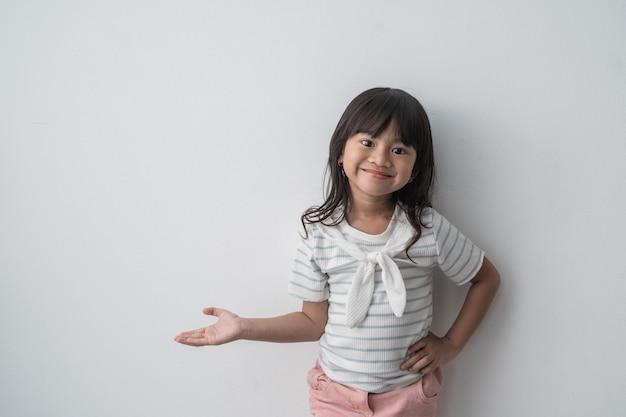 Niña asiática que sonríe mostrando la mano