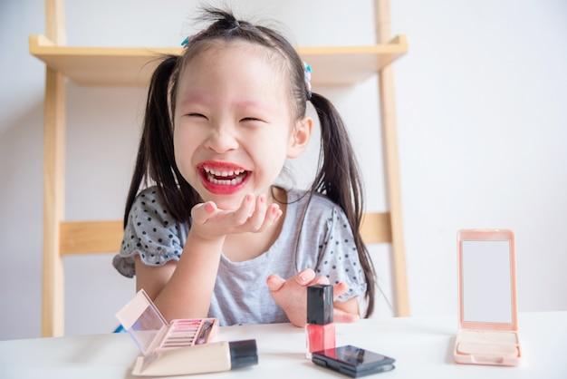 Niña asiática riendo después de maquillaje cara por sí misma
