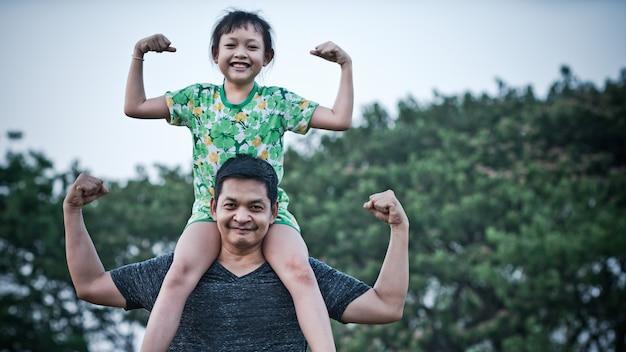 Niña asiática sentada sobre los hombros de su padre y hacer gestos de acción fuerte con una sonrisa y feliz.concepto del día del padre