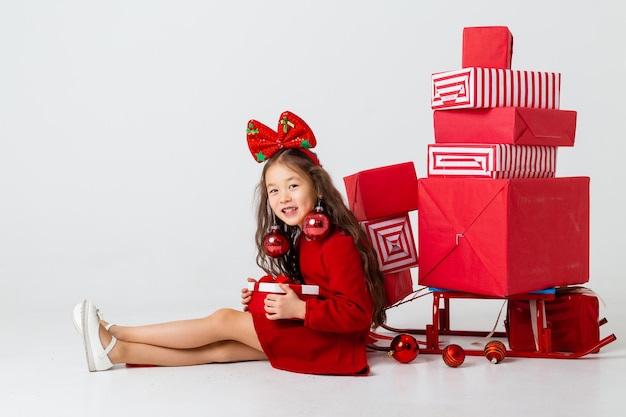 Una niña asiática sentada en un vestido rojo se sienta con cajas de regalo sobre un fondo blanco. concepto de navidad, espacio de texto