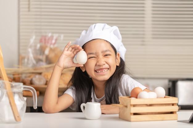 Niña asiática con un sombrero de chef blanco está sosteniendo un huevo de pato