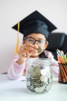 Niña asiática con sombrero de graduado poniendo una moneda en frasco de vidrio transparente