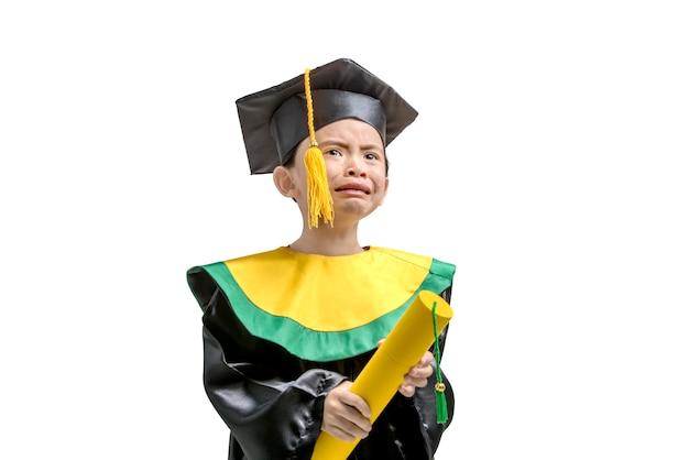 Niña asiática en sombrero y toga de graduación con certificado llorando