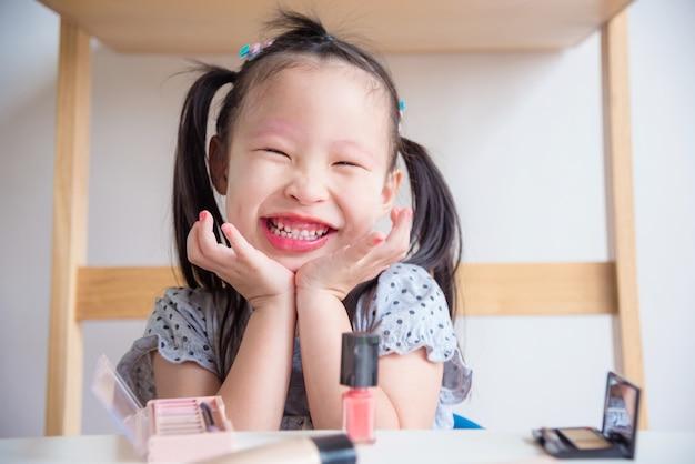 Niña asiática sonriendo felizmente después de hacer la cara sola