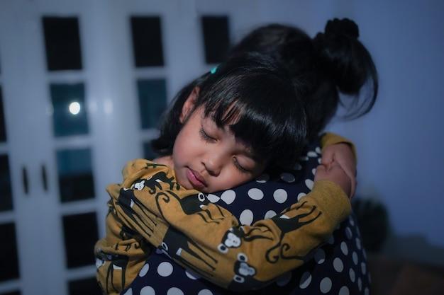 Niña asiática con sueño está durmiendo en el brazo de su madre.