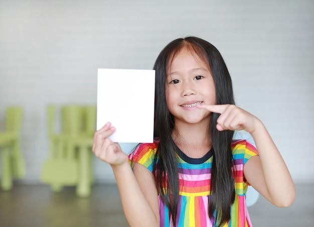 Niña asiática con tarjeta de papel blanco en blanco en la mano