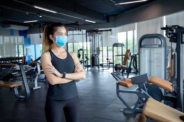 Niña asiática usa una máscara de anatomía para hacer ejercicio en el gym para evitar creer virus