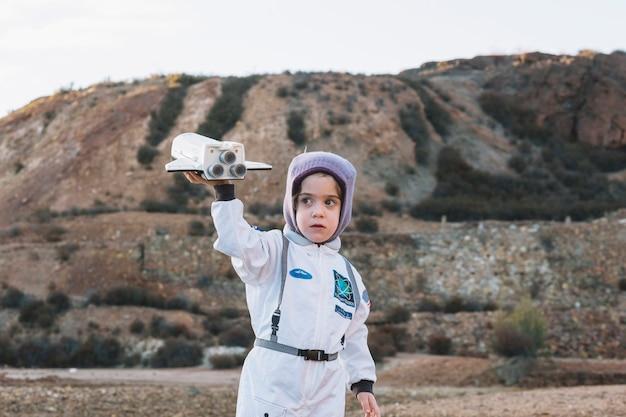 Niña astronauta jugando en la naturaleza