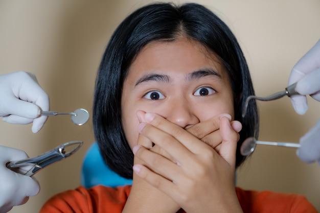 Niña asustada por los dentistas cubre su boca en la oficina del dentista
