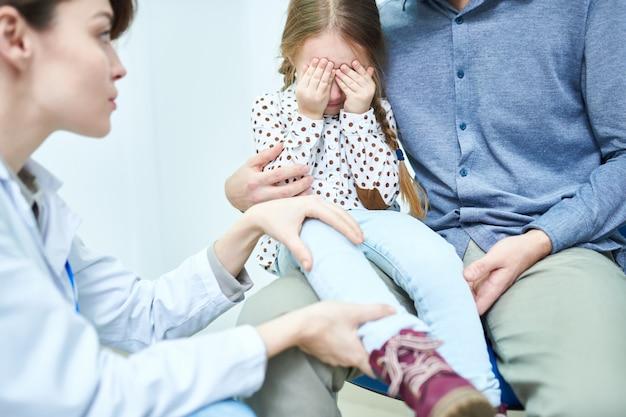 Niña asustada con los ojos cerrados por las manos en la cita con el médico