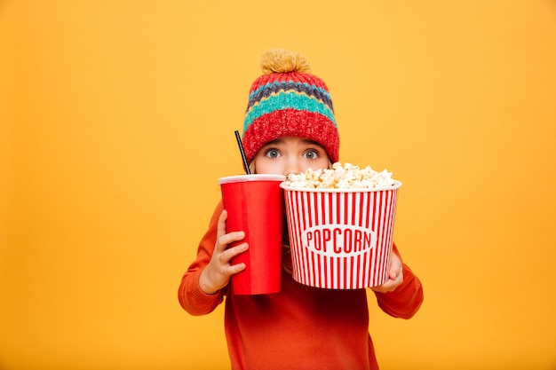 Niña asustada en suéter y sombrero escondiéndose detrás de las palomitas de maíz y un vaso de plástico mientras mira a la cámara sobre naranja