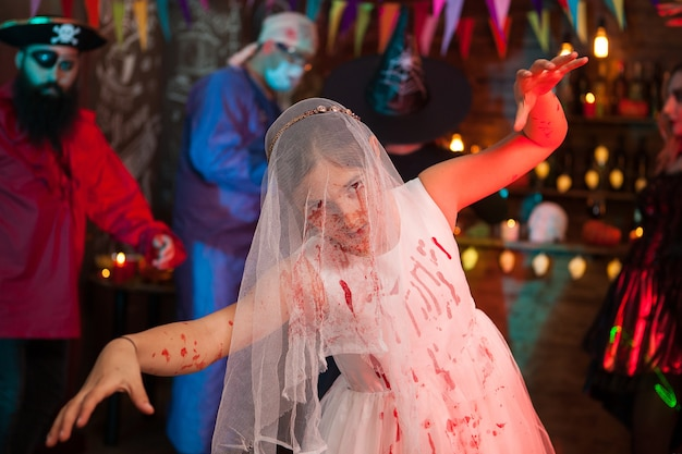 Niña asustadiza en una fiesta de halloween vestida como una novia con vestido de deshierbe. pirata aterrador en el fondo.