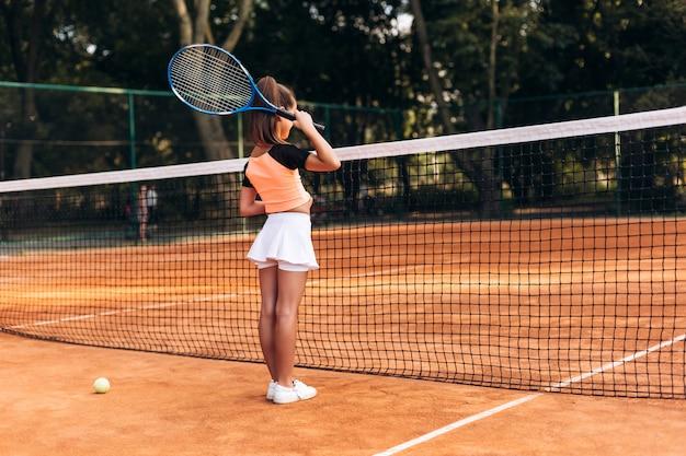 Niña atractiva en ropa deportiva está jugando tenis