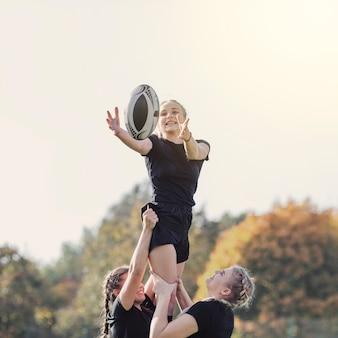 Niña atrapando una pelota ayudada por sus compañeros de equipo