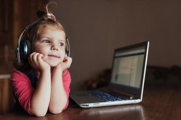 Niña con auriculares escuchando música, usando una computadora portátil