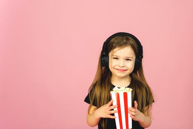 Niña con auriculares grandes mira una película, come palomitas de maíz y sonríe sobre un fondo rosa pastel