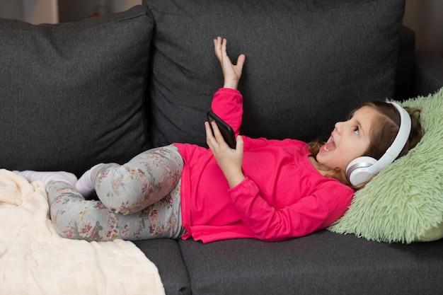 Niña en auriculares inalámbricos escalofriante riendo en el sofá escuchando música favorita con teléfono usando la aplicación móvil de reproductor en línea. disfruta de un estado de ánimo tranquilo usando auriculares en casa