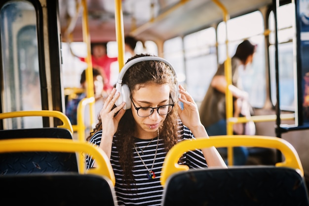 Niña con auriculares sentado en un autobús