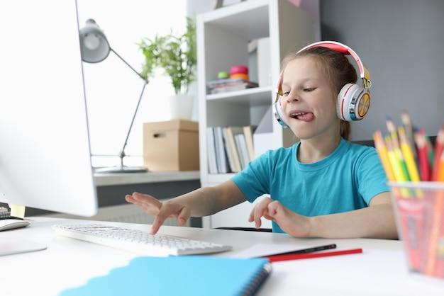 Niña en auriculares sentado en la mesa y escribiendo en el teclado de la computadora