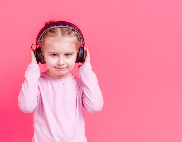 Niña en auriculares sobre fondo rosa