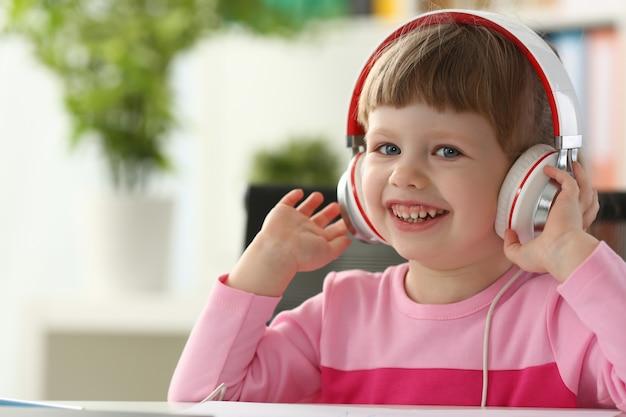Niña con auriculares usar computadora móvil