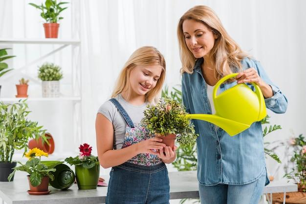 Niña ayudando a mamá a regar flores
