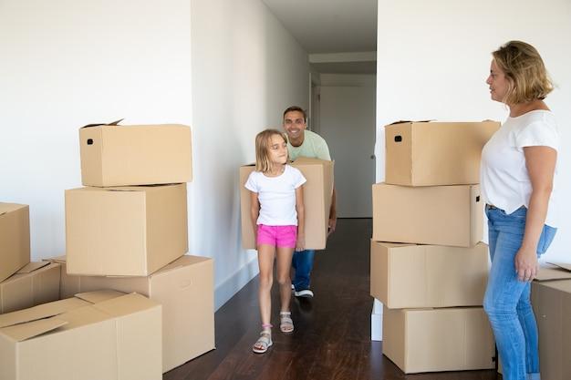 Niña ayudando a los padres a mudarse a un nuevo apartamento