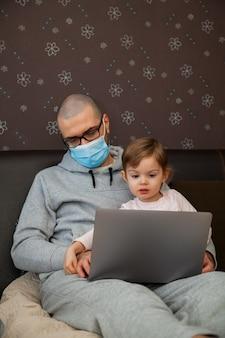Niña ayudando a su padre a trabajar en una computadora portátil