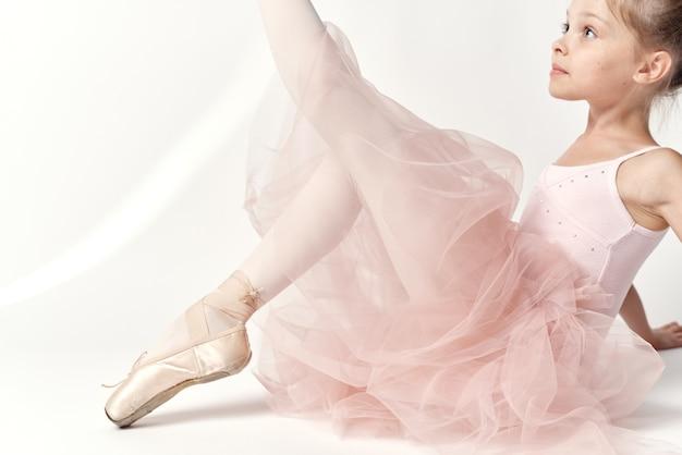 Niña bailarina en un traje blanco en zapatillas de punta