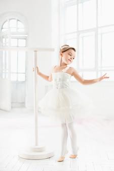 Niña bailarina en un tutú. adorable niño bailando ballet clásico en un estudio blanco.