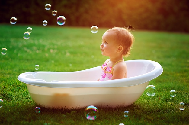 Niña se baña en un baño con pompas de jabón