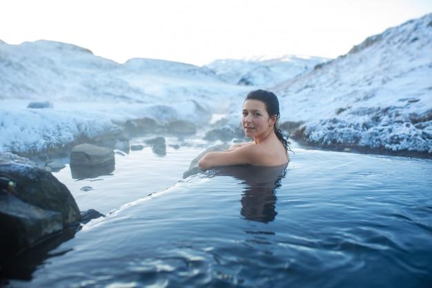La niña se baña en una fuente termal al aire libre con una hermosa vista de las montañas nevadas. islandia increíble en invierno