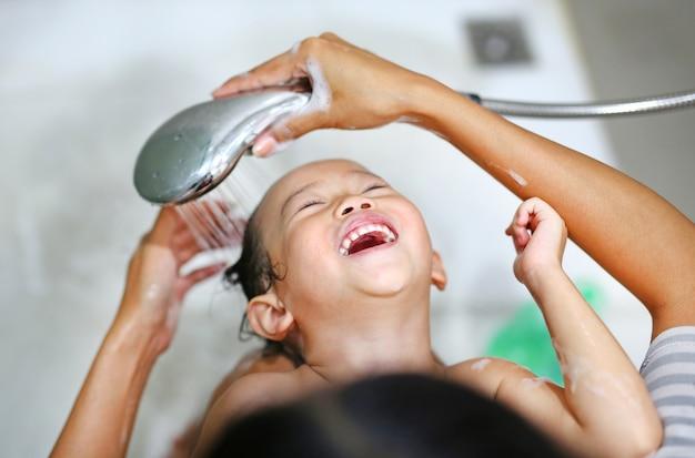 Niña bañándose y lavada con champú por su madre