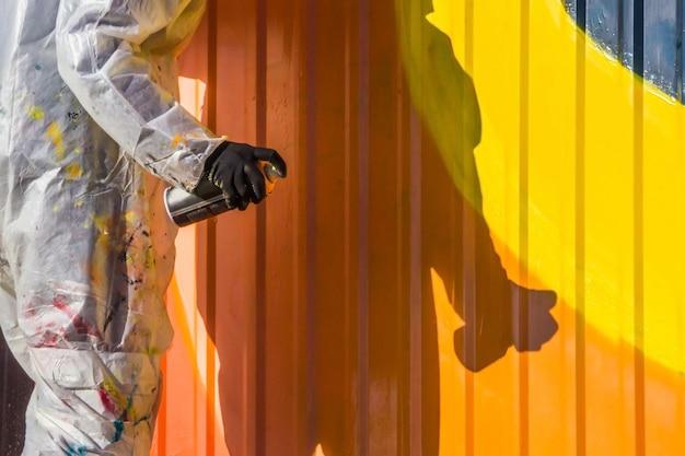 Una niña con una bata blanca con manchas de pintura pinta graffiti valla de hierro acanalado