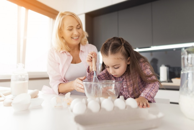 Una niña está batiendo huevos con un batidor