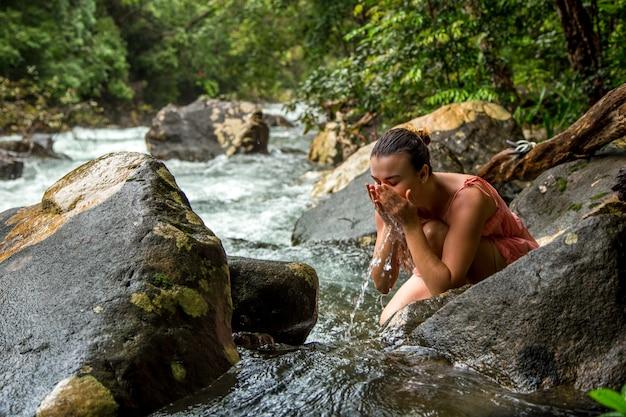 La niña bebe agua de un arroyo de montaña