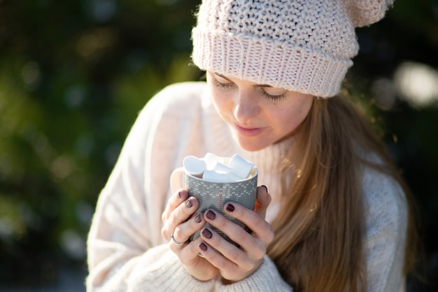 Niña bebe una bebida caliente con malvaviscos en el invierno en el bosque.