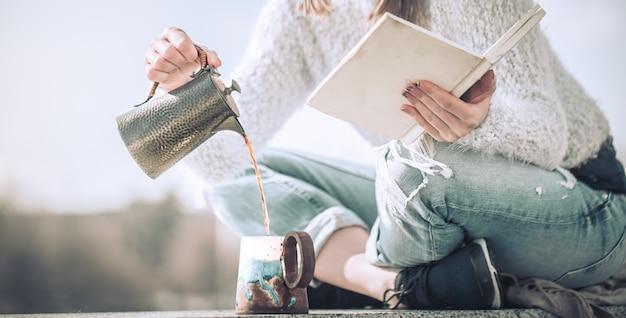 Niña bebe café y lee libros al aire libre
