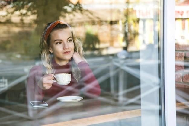Niña bebe capuchino en una cafetería sentado en una mesa junto a la ventana.