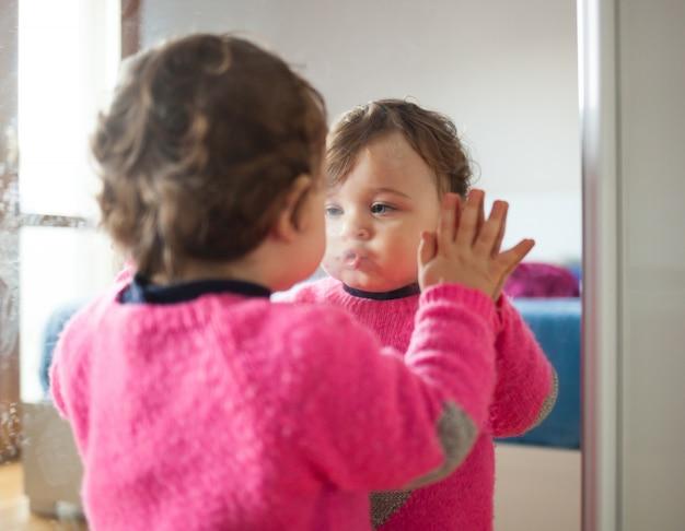 Niña bebé jugando con espejo en el dormitorio