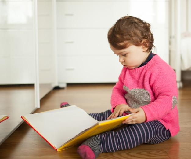 Niña bebé jugando con libro de cuentos de hadas