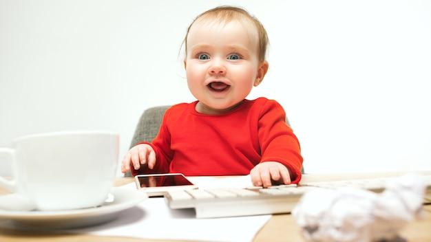 Niña bebé sentado con el teclado de la computadora moderna o portátil en el estudio blanco.