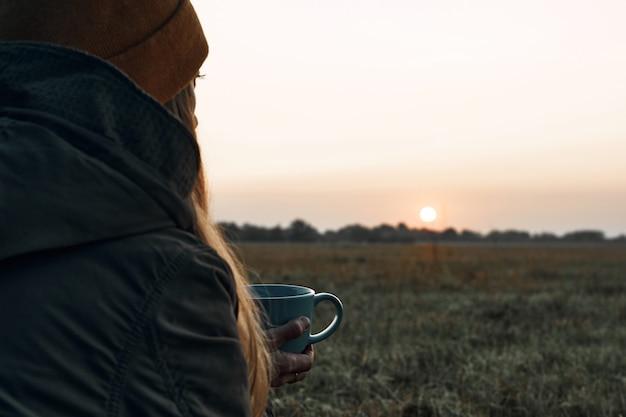La niña bebe de una taza y mira el frío amanecer. viajes.