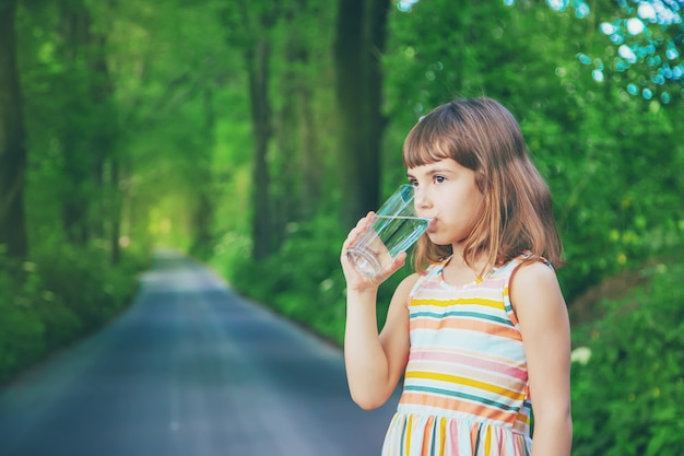 Niña bebiendo agua de un vaso