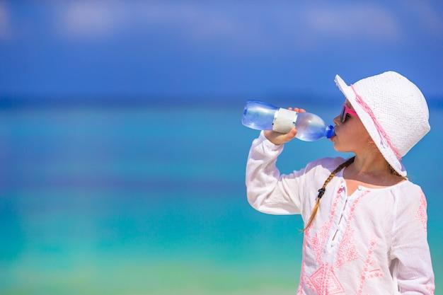 Niña bebiendo una botella mineral de agua en un caluroso día de verano en la playa
