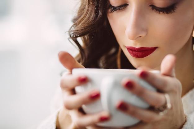 Niña bebiendo café en una cafetería de moda