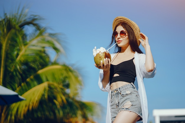 Niña bebiendo jugo fresco de un coco junto a la piscina