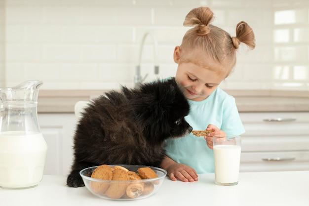 Niña bebiendo leche y jugando con perro en casa